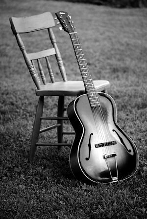 Black and white acoustic guitar against wooden chair by ben mancino