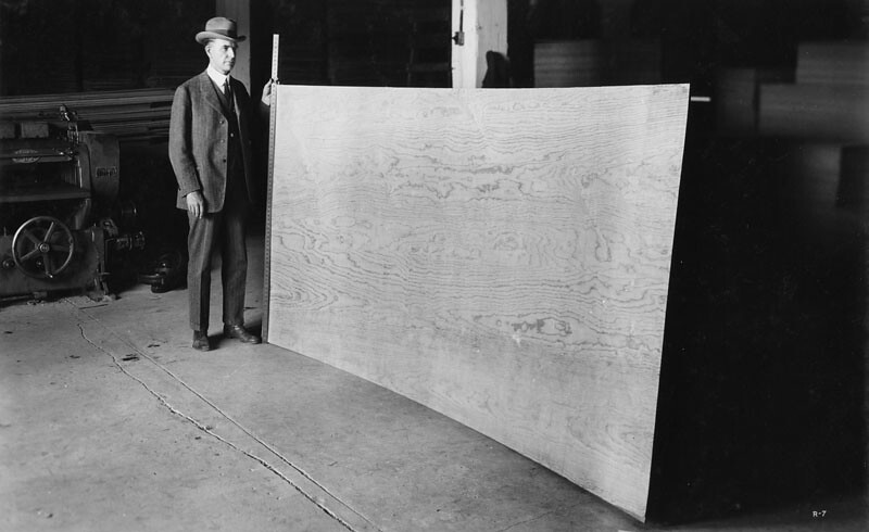 Measuring wood. | Caption: [Man standing and measuring ...