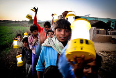 All smiles while taking their respective lanterns home from the solar charging station (in the background) by Jarnail Singh, Heller School