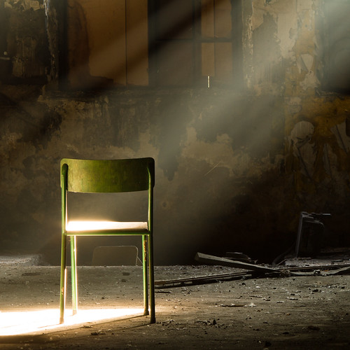 A lone green chair in a dark dirty room, a ray of sunlight shines through the window on the green chair | by crsan