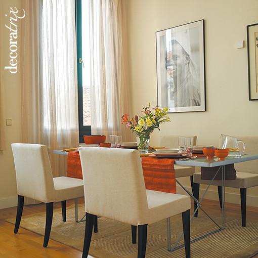 En el comedor mesa de cristal y sillas tapizadas en el for Sillas con apoyabrazos tapizadas