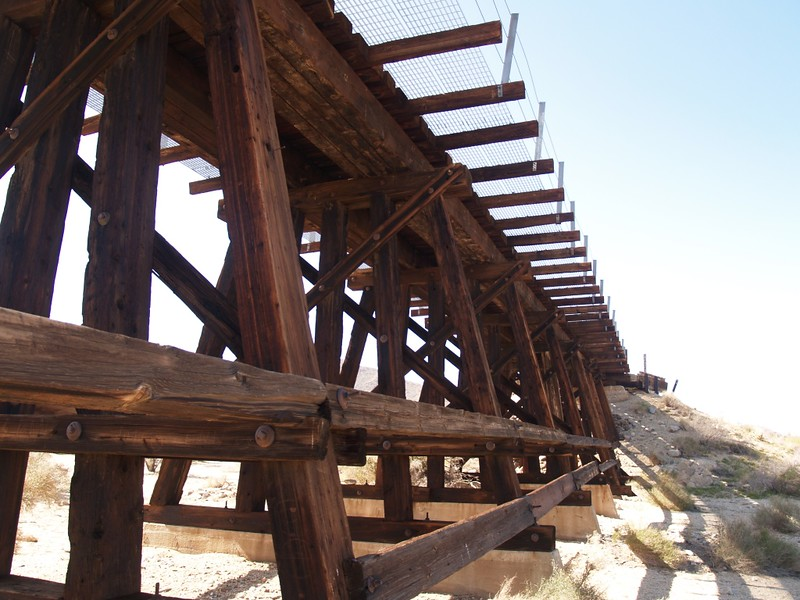 Looking up at the wooden trestle and catwalk from the dry wash north of Dos Cabezas