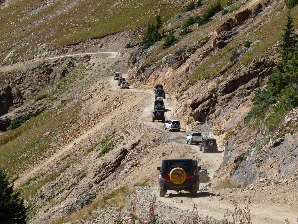 Caravan Of Jeeps And Other Vehicles On Red Mountain Outsid