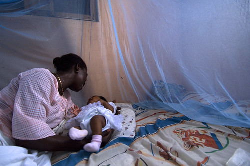 Mother place infant unto a  bed surrounded by protective malaria bed net | by World Bank Photo Collection