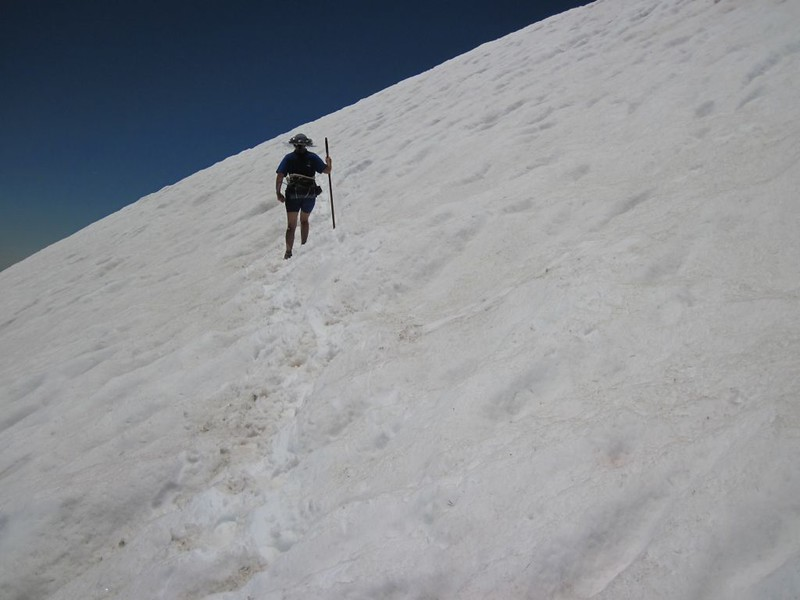 Vicki crossing the sloping snowfield carefully, using her stick for balance