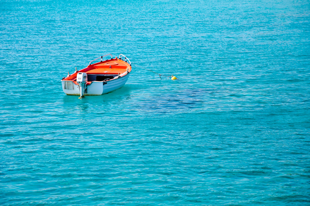 white empty boat floating on turquoise sea waters