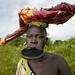 Surma girl bringing cow meat - Ethiopia
