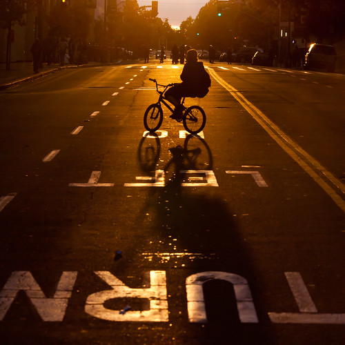 Protestor on Bicycle With Riot Cops in Distance as Sun Begins to Set, Oakland Riots, 2010 | by Thomas Hawk