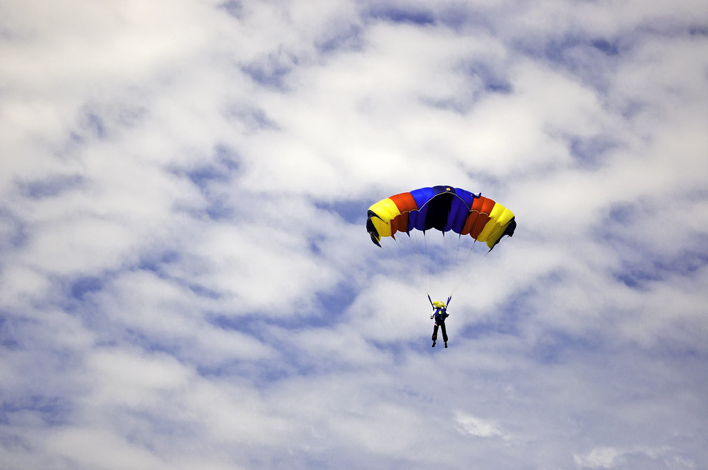 Parachute jumper against cloudy sky | Man jumping with a ...