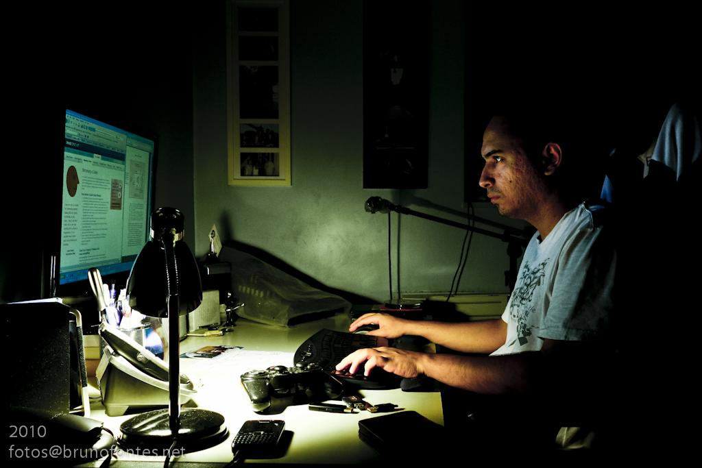 man sitting at dark desk typing on the computer