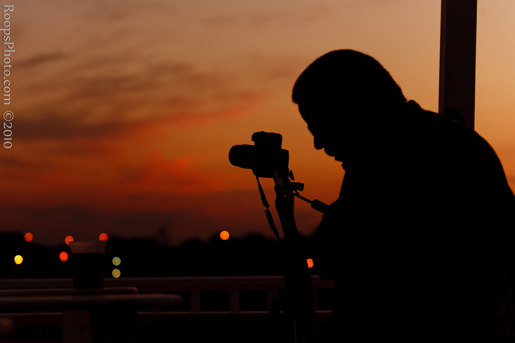 silhouette of photographer capturing the sunset. Black Bedroom Furniture Sets. Home Design Ideas