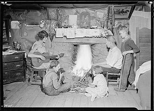"""The Glandon family around the fireplace in their home at Bridges Chapel near Loydston[sic], Tennessee. Glandon's wife plays both the guitar and the organ."", 10/31/1933 