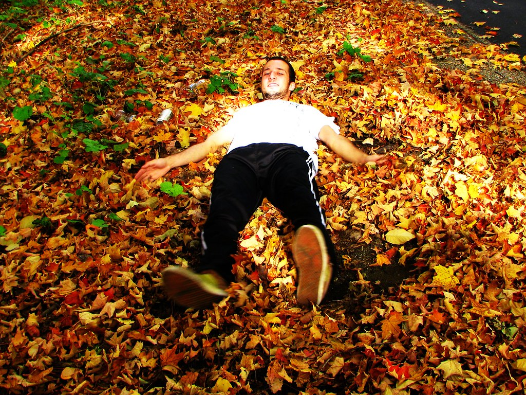 Man lying on autumn leaves