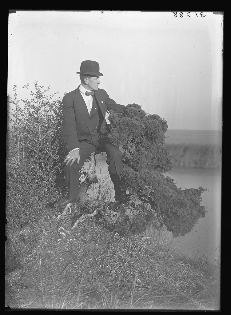 huron h smith in suit bow tie and bowler hat by the field
