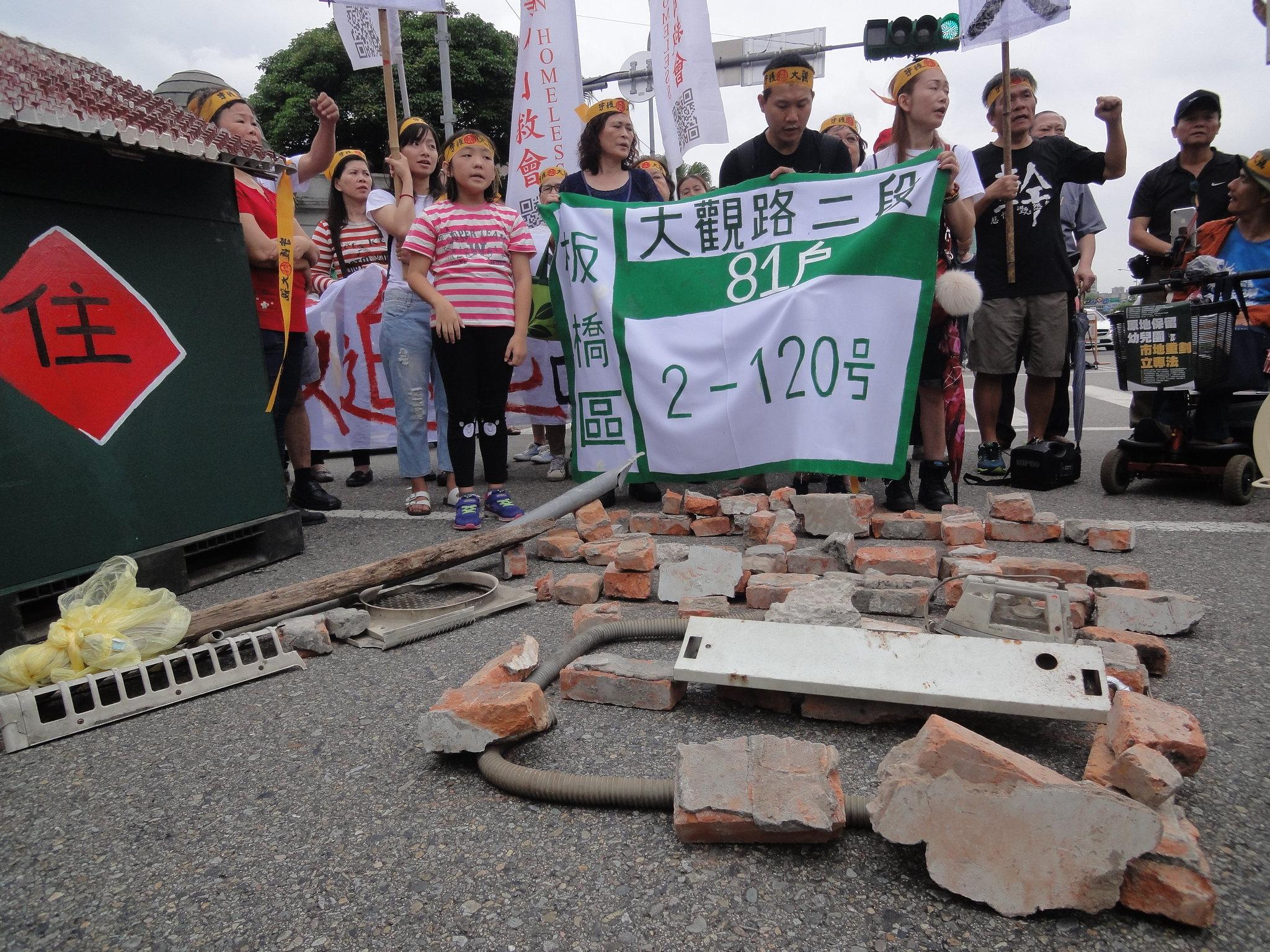 石塊、瓦礫排成的「厝」字,表達了居民捍衛家園的信念。(攝影:張智琦)