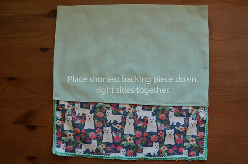 12. Place first backing piece on fabric, right sides together. Double-folded hem horizontally in the middle.