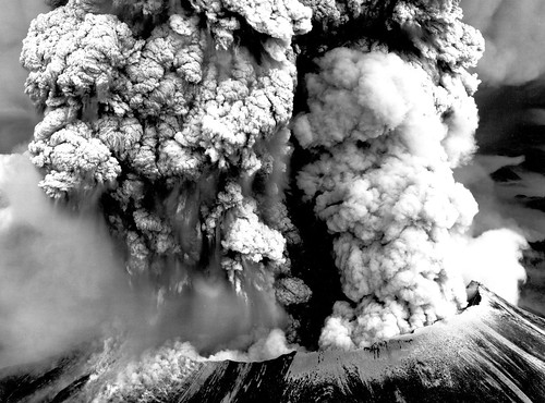 Black and white image shows the truncated summit of Mount St. Helens, with a cauliflower cloud of ash boiling from it.