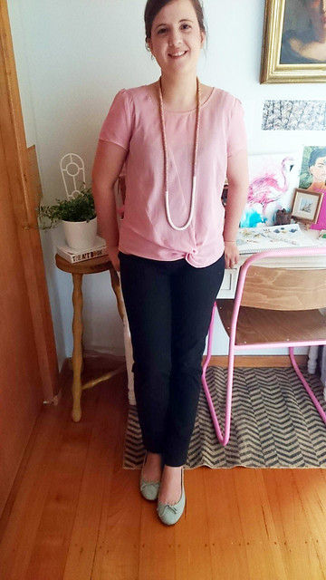 A woman wears dark skinny jeans, pink tee and blue flats.