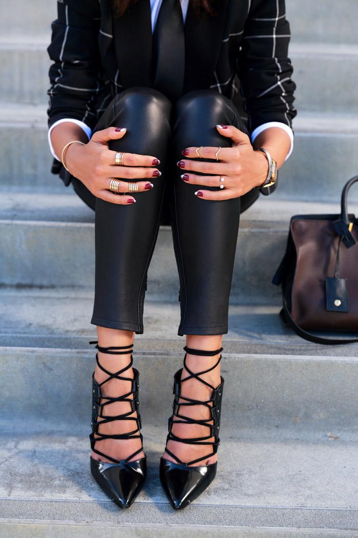 ragazza che indossa sandali con tacco neri lucidi e leggins di pelle