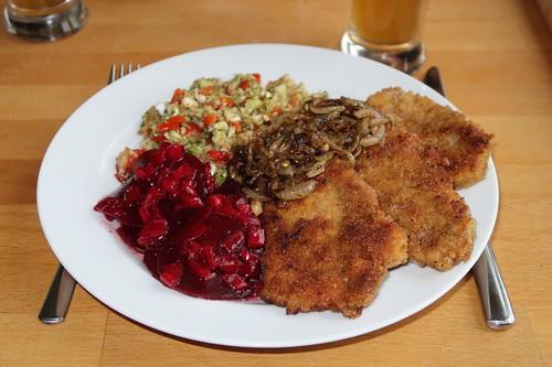 Panierte Schnitzelchen mit geschmorten Zwiebeln und Resten der Salat vom Grillen