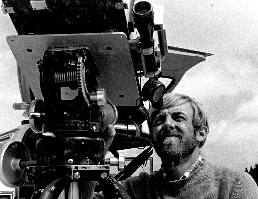 Black and white photo shows a young bearded man with short, light-colored hair, squinting into a bulky instrument that looks something like a huge movie camera.