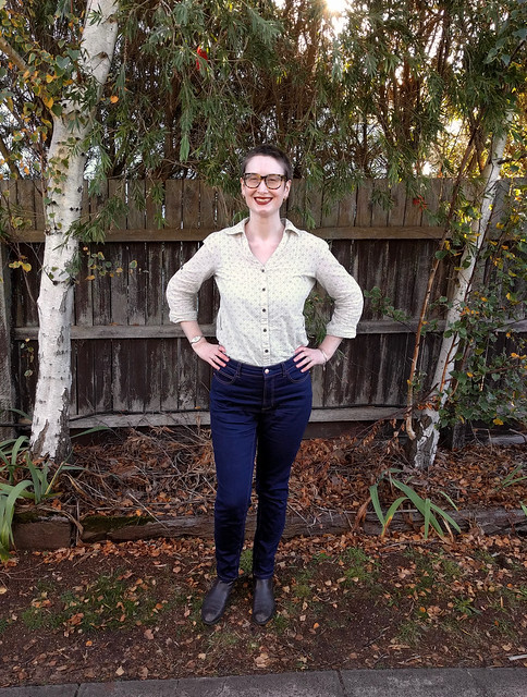 A woman stands in front of a garden fence. She wears dark blue, slim jeans and a button up shirt.