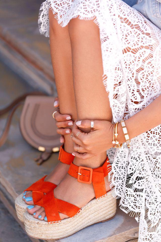 ragazza con sandali espadrillas arancioni aperti e gonna di pizzo bianca