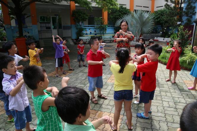Với học sinh lớp 1, đến trường là để được vui chơi, ca hát, giao tiếp với bạn bè cùng trang lứa. Trong ảnh: học sinh lớp 1 Trường tiểu học Châu Văn Liêm, Q.6 (TP.HCM) trong buổi sinh hoạt ngoài trời - Ảnh: NHƯ HÙNG