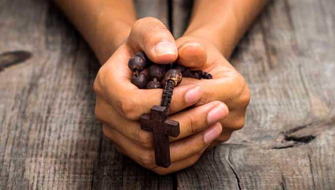 imagen de manos con rosario representando los arcángel Uriel rezando