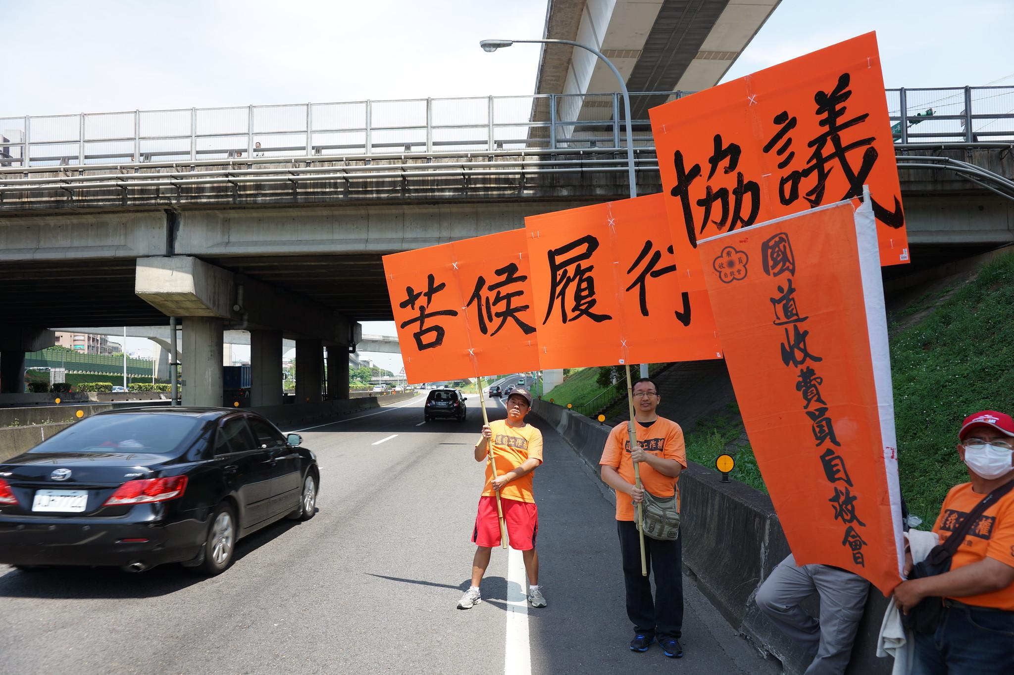 在國道路肩高舉「苦候」、「履行」、「協議」牌。(攝影:王顥中)