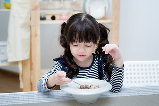 Asian child eat cereal and milk | by anekphoto