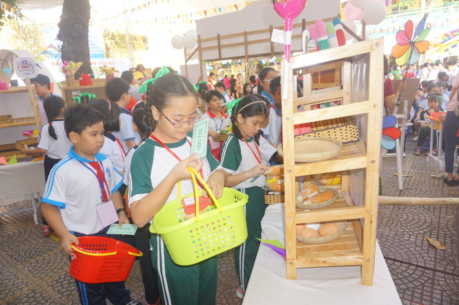 """Học sinh được phát """"phiếu siêu thị"""" để đi mua đồ dùng, đồ chơi sao cho không dư và không thiếu tiền - Ảnh: H.HG."""