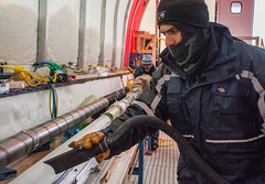 Murat Aydin cleans drilling fluid off a rent ice core as he prepares it for storage