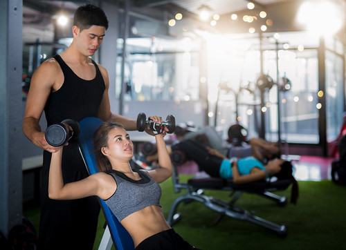 Asian trainer and lady take personal training in fitness club | by anekphoto