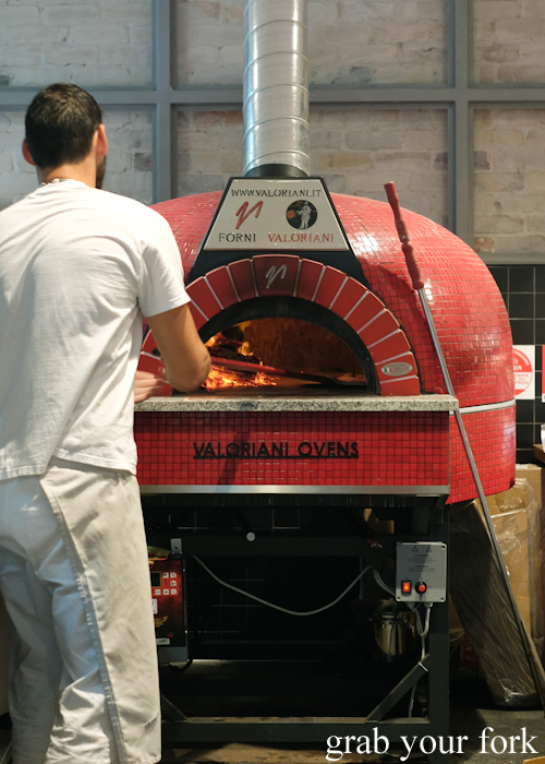 Pizza Mario cooking pizzas in the woodfired oven at the Merchants of Ultimo at Broadway Shopping Centre