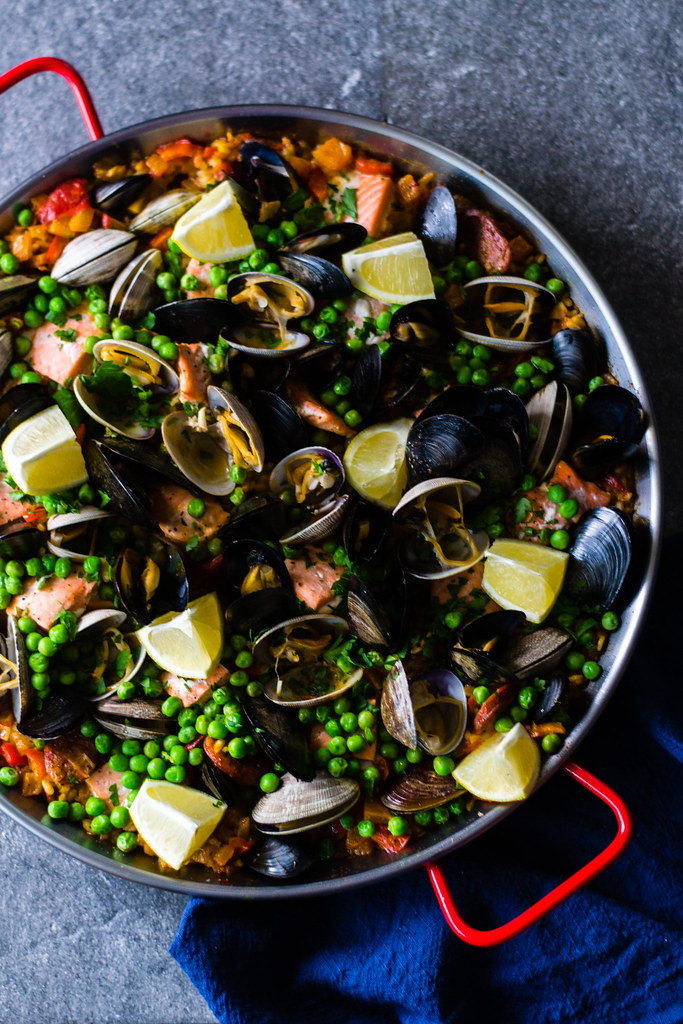 Seafood and chorizo paella recipe is full of Pacific Northwest clams and mussels, wild salmon, spicy chorizo and garnished with sweet peas and bright lemon.
