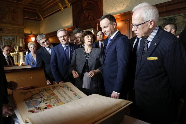 """President of Poland Andrzej Duda looks over collection items from the 1926 """"Polish Declarations of Admiration and Friendship to the United States"""" with European Division specialist Regina Frackowiak (center left) and Chief of Staff Robert Newlen (right) during a visit to the Library, March 31, 2016. Photo by Shawn Miller. From Unexpected Treasures at America's Library: Heartfelt Friendship Between Nations"""