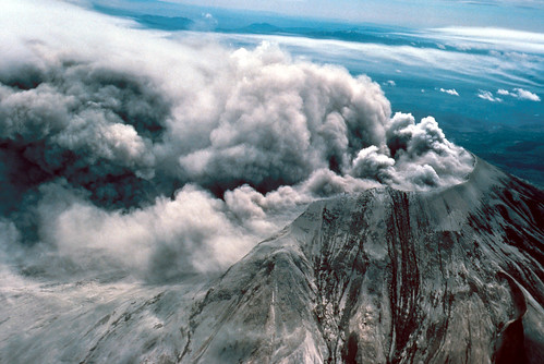 Color image shows the truncated summit of Mount St. Helens, covered in brownish-gray ash. Thick, low clouds of ash still boil from the gaping crater where her summit used to be.