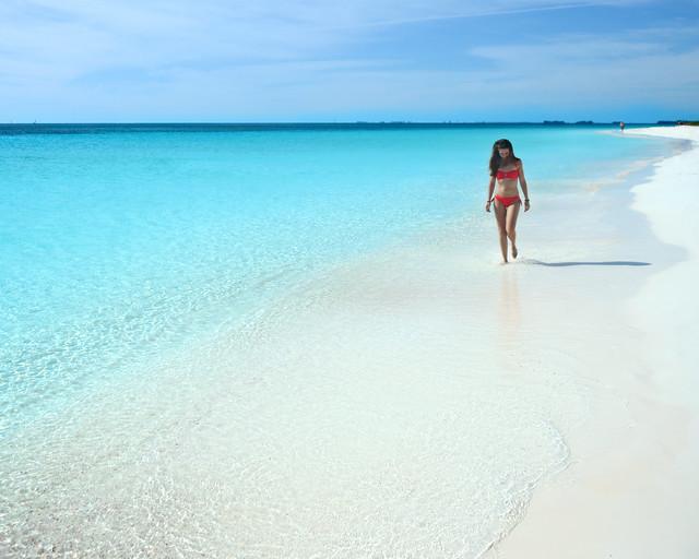 Diana paseando por la orilla de playa Sirena y su color azul eléctrico