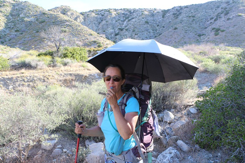 Vicki has her chrome umbrella deployed on her backpack and is ready to hike in the sun