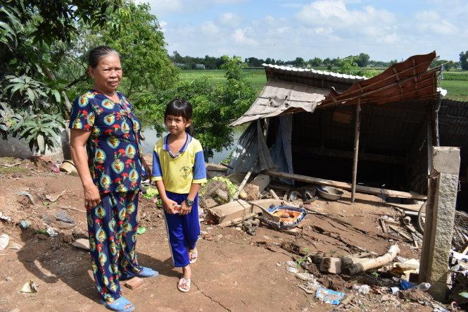Hai bà cháu này có nhà bị sạt lở xuống kênh Cỏ Lau mới không có nơi ăn ở- Ảnh: Bửu Đấu