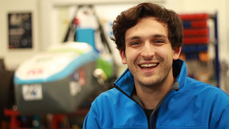 Stefano smiles in front of the Team Bath Racing Electric race car.