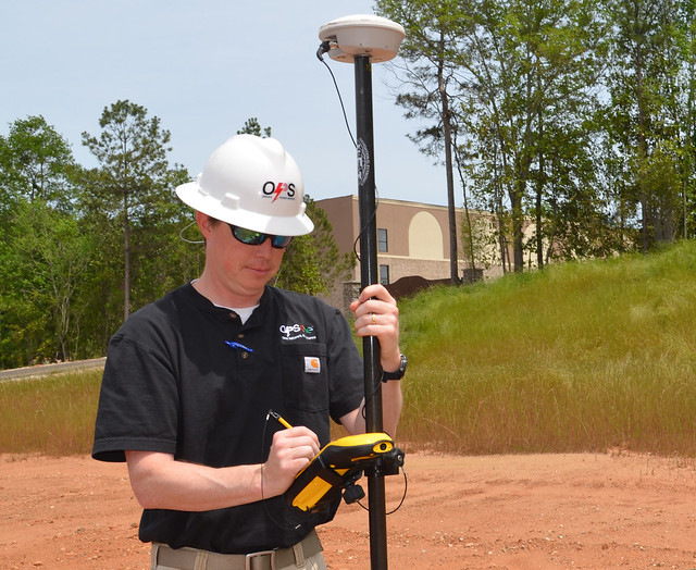 Larry Prince uses a GPS device to plot fiber optics and electrical services.
