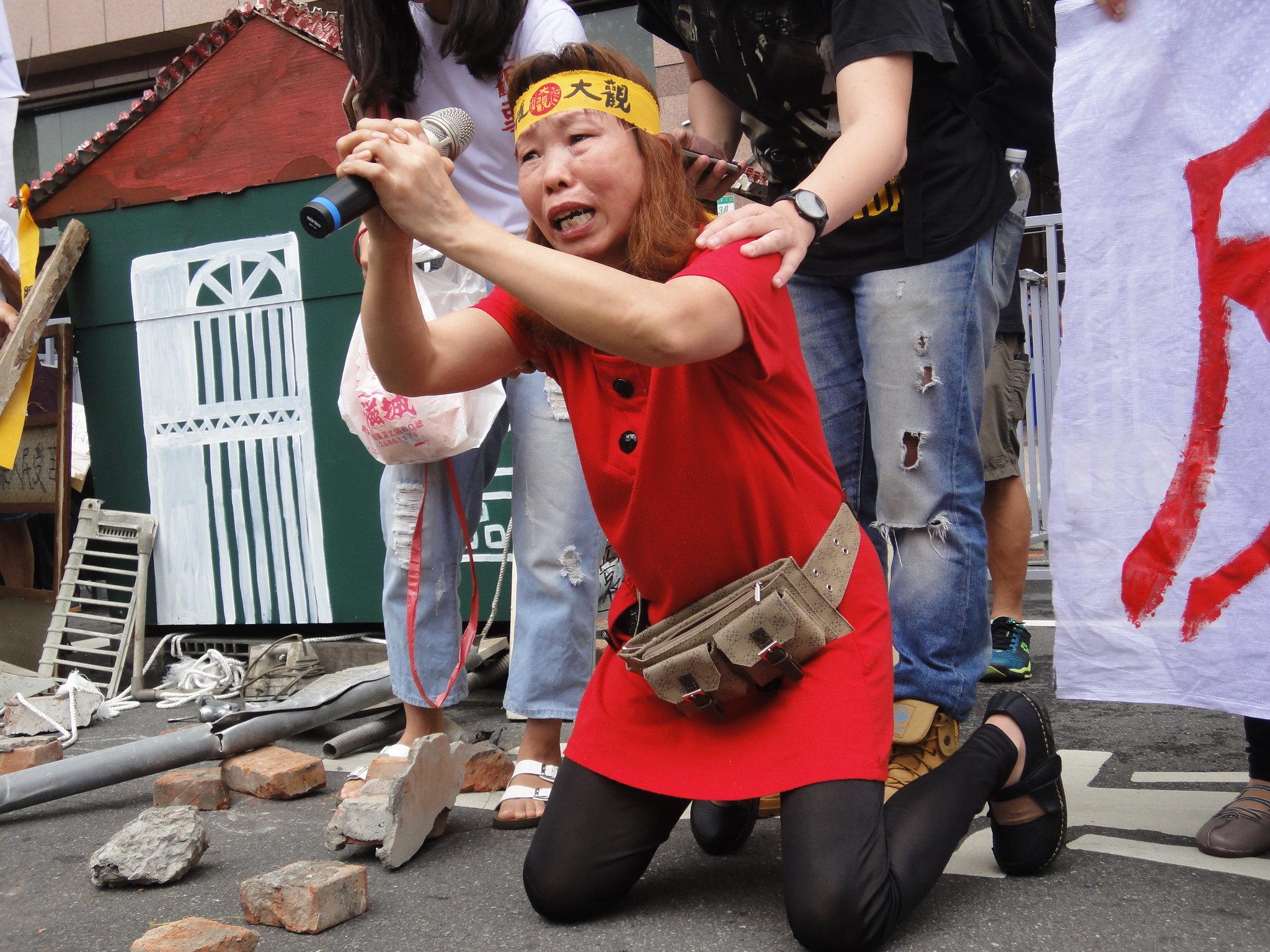居民湯家梅在民進黨部前下跪,請求政府不要讓她無家可歸。(攝影:張智琦)