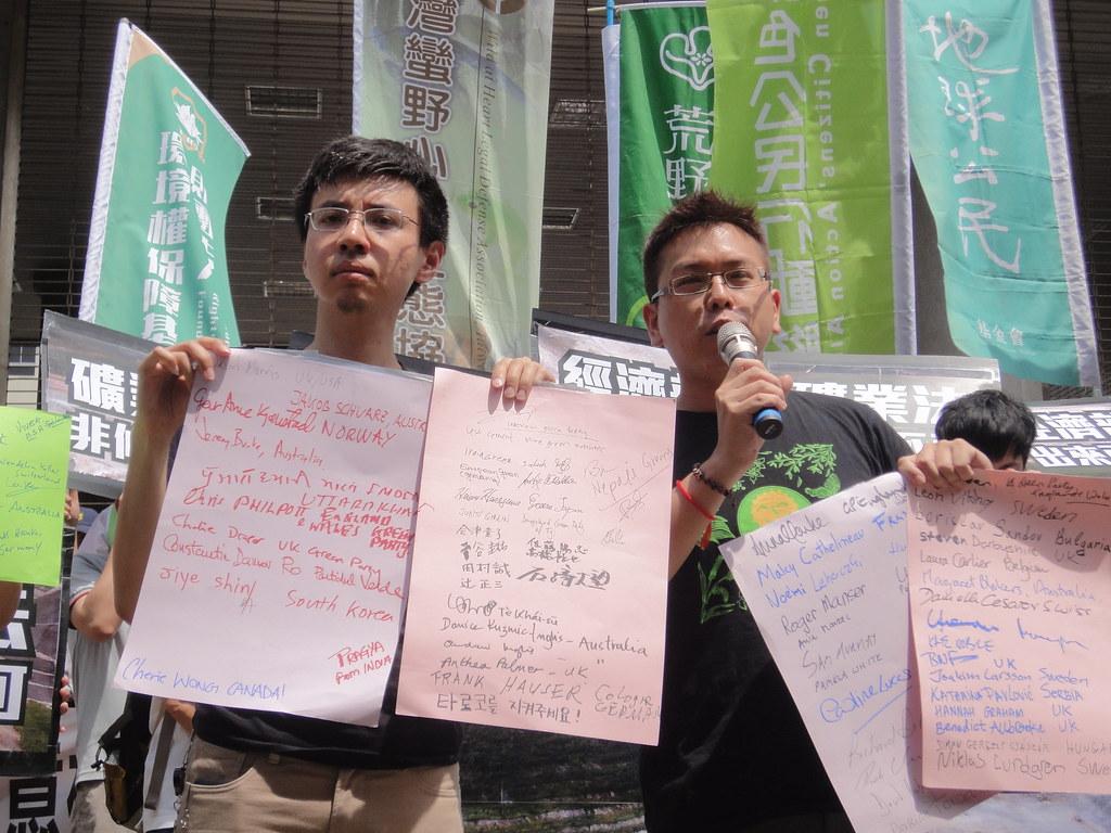 綠黨拿出各國綠黨政治人物連署反對亞泥展延的名單。(攝影:張智琦)