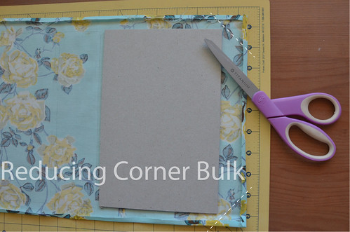 "22. Trim 4 corners off book cloth at 45 degree angle, 1/16"" away from the book board."