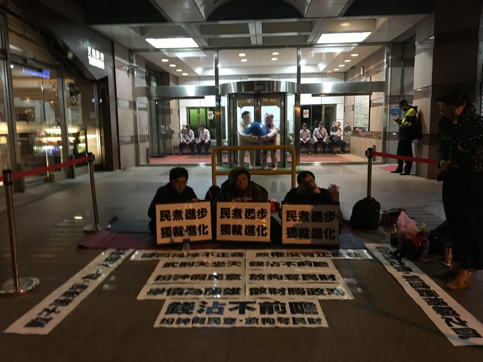 晚間7點多,天氣轉冷,並開始下雨,徐世榮與支持者仍然在民進黨部前靜坐,用行動表達「公民不服從」。(攝影:陳逸婷)
