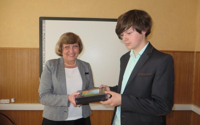 Представитель ДТЭК вручает планшет семикласснику Карабиновской школы Артему Знову