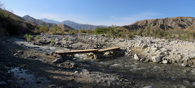 A wooden bridge crosses the Whitewater River on the Whitewater Preserve Trail