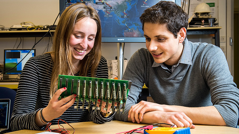 Two students sat in a laboratory looking at a circuit board